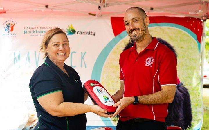 Carinity Education Rockhampton Principal Lyn Harland presents a first aid kit to Joseph Pickett from Eddie's Van.