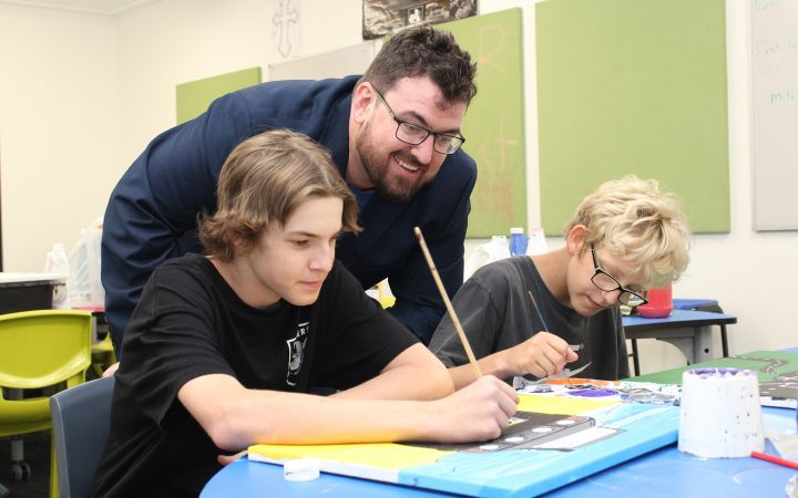 Carinity Education Rockhampton teacher Mitchell McAulay-Powell assists students Ford Peckover and Alexander Luckerbauer during art class