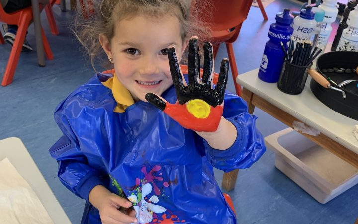Shalom Student painting hands for Reconciliation Week