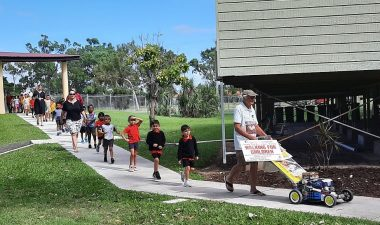 Shalom Christian College students follow Claude The Mower Man Harvey on a lap of the school campus with his trademark lawnmower